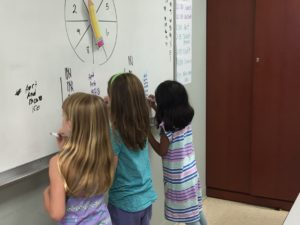 whiteboard--students write letters in words