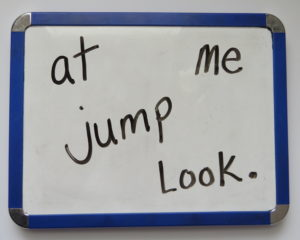 Look at me jump words written in scrambled fashion on a whiteboard.