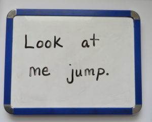 "The sentence, ""Look at me jump."" written correctly on an individual whiteboard."