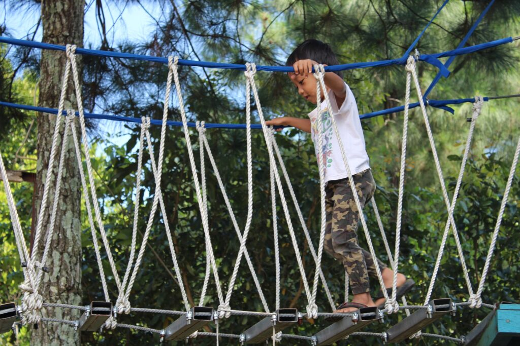 A boy walking across a rope bridge